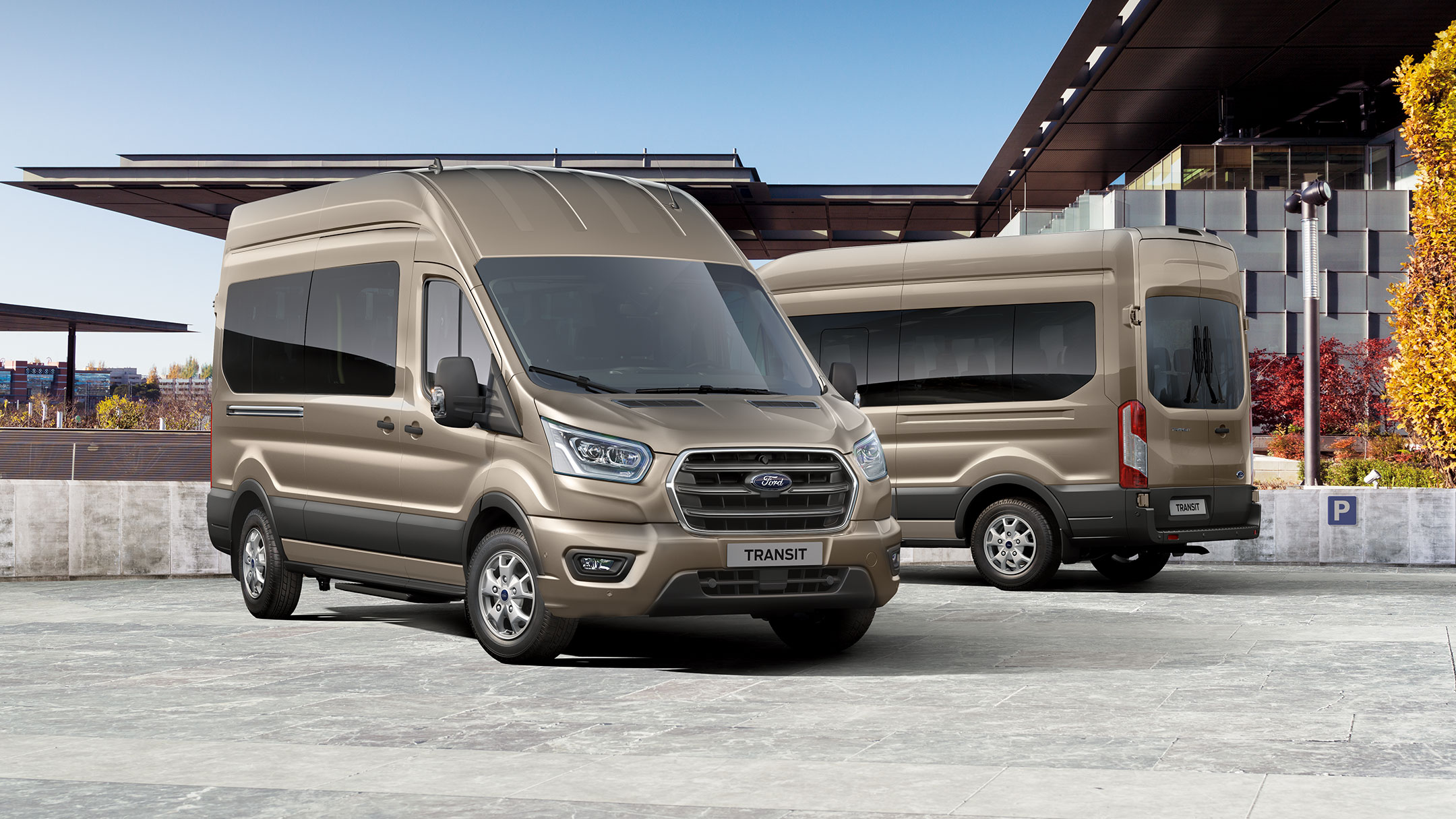 Two New gold Ford Transit Minibuses parked side by side