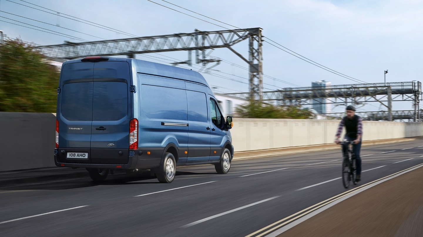 New Blue Transit Van rear view driving on road