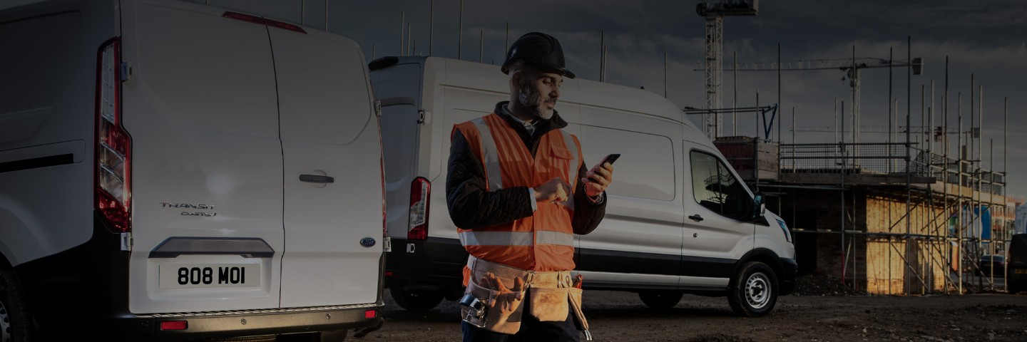 Ford Transit vehicles parked at a building site with a man looking at his smartphone