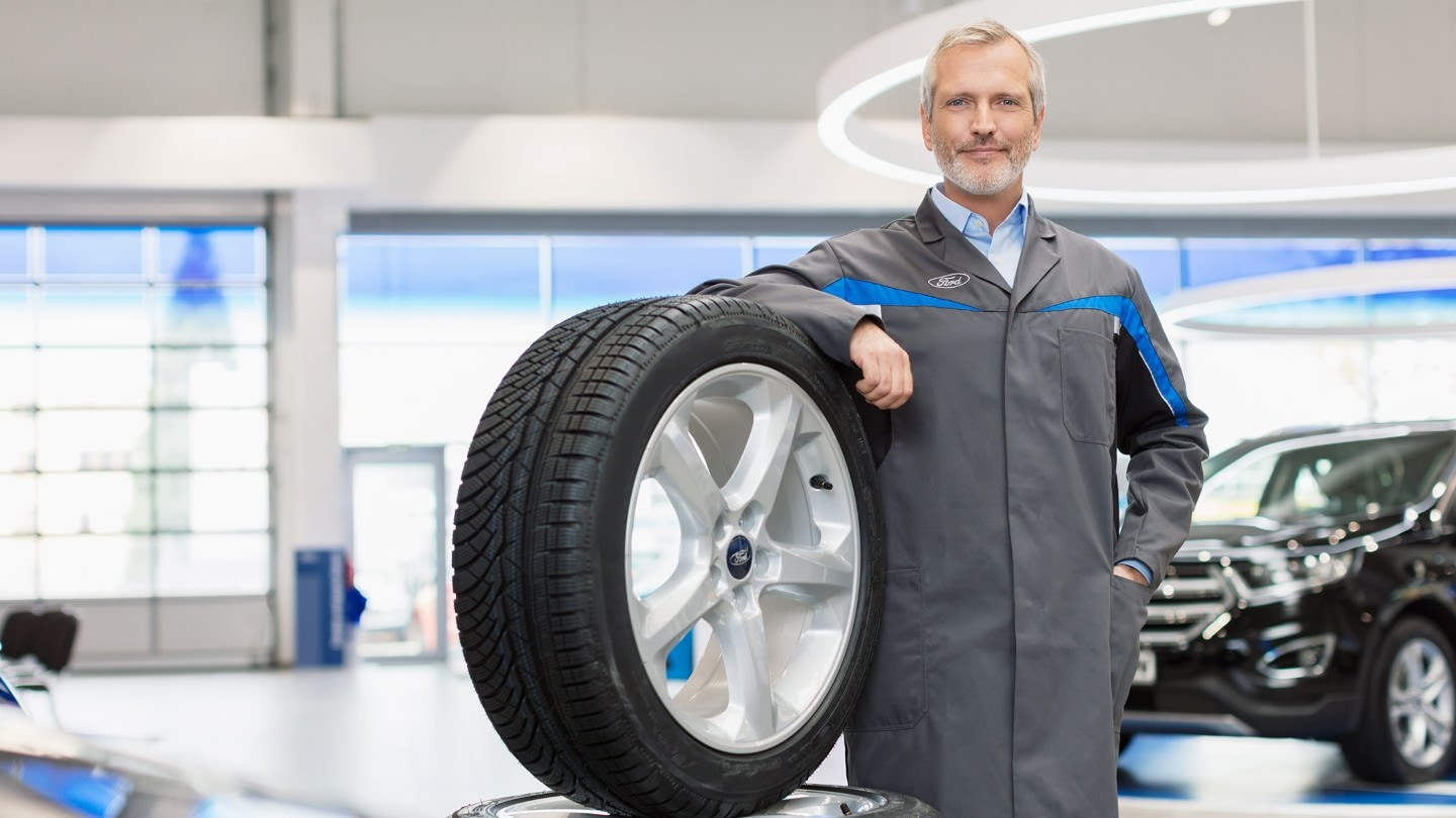 A mechanic holding a wheel at Ford Repair Centre