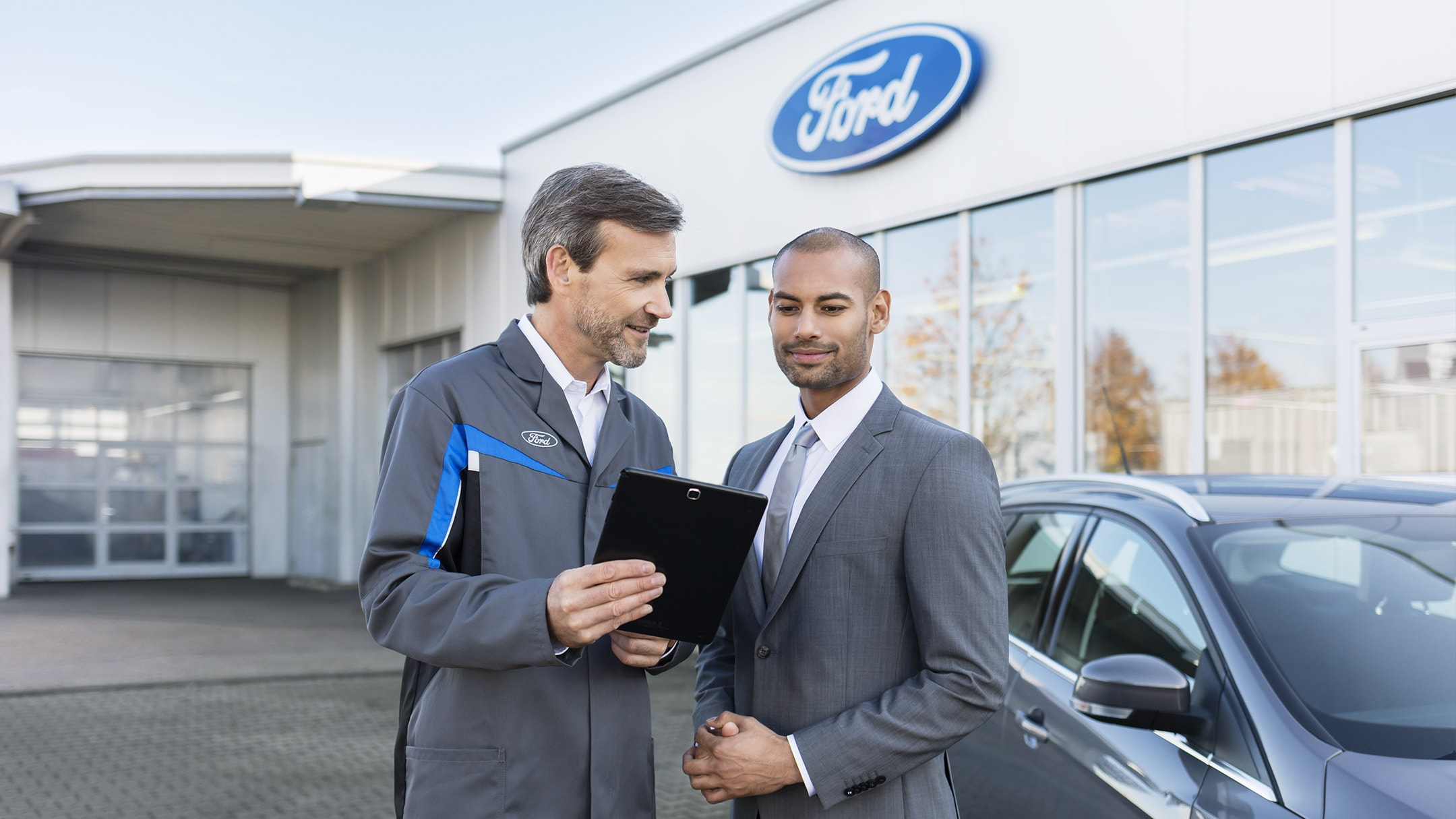 Two men in front of Ford dealership