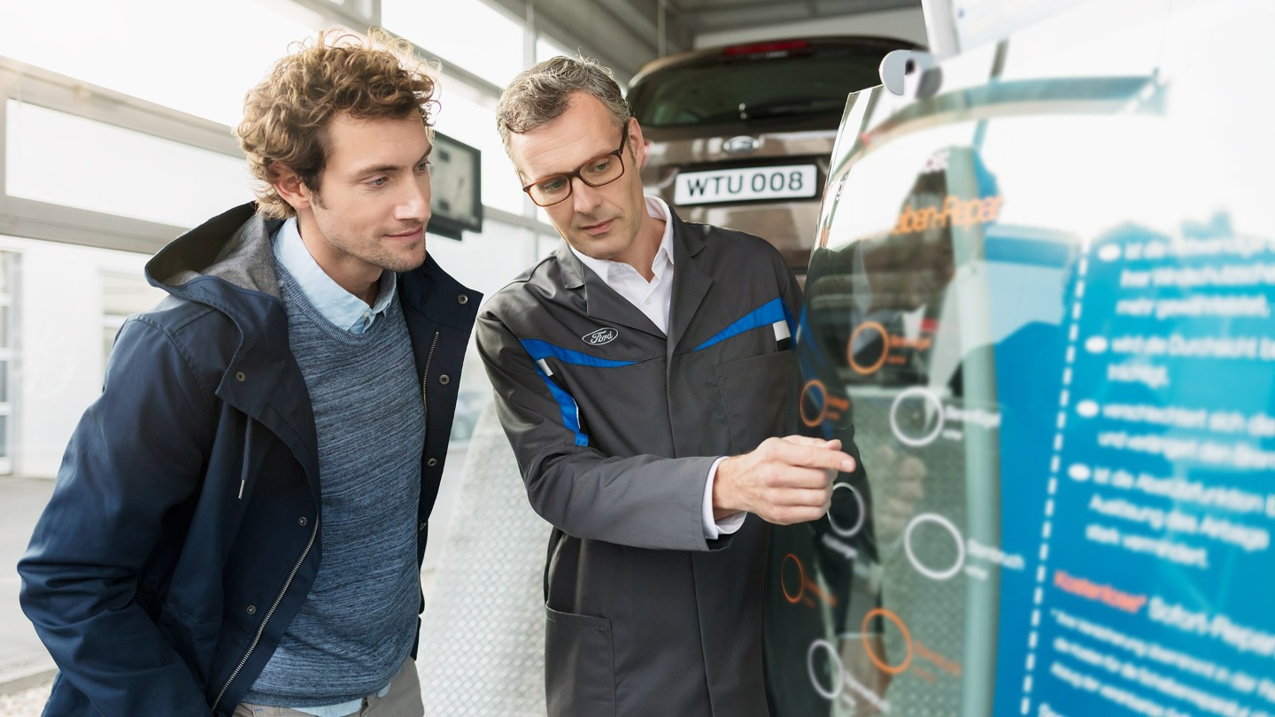 A mechanic discussing tyres with a client at Ford