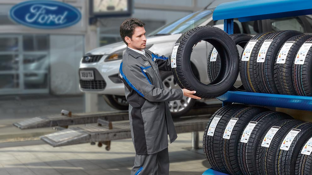 A mechanic checking tyre label at Ford